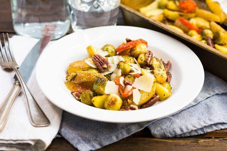 Recept voor geroosterde aardappelen & spruiten voor 4 personen. Met olijfolie, peper, bakpapier, spruitjes, trostomaat, aardappelen kruimig, rozemarijn, knoflook, piri piri en pecannoten