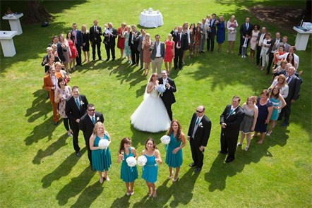 Omringd door liefde <3! Een trouwfoto van bovenaf gemaakt, met het bruidspaar in het midden en de vrienden/familie eromheen in een hartvorm.