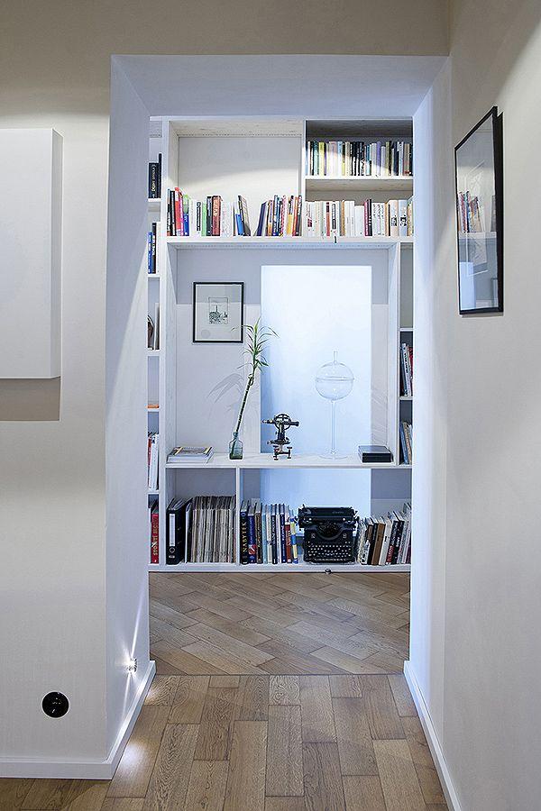 Knihovna navržená na míru propouští do vstupní haly denní světlo skrze mléčné prosklení do kuchyně. Volný přechod haly do obytného prostoru je zdůrazněn změnou směru parket. | Edit!