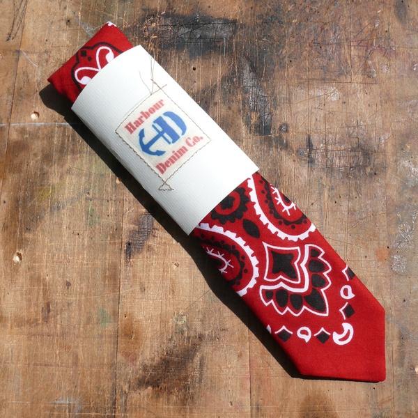Klassische schmale Krawatte aus einem Original-Bandana, auf Baumwolleinlage von Hand verarbeitet. Die Krawattenspitzen sind mit einer roten Viscose...