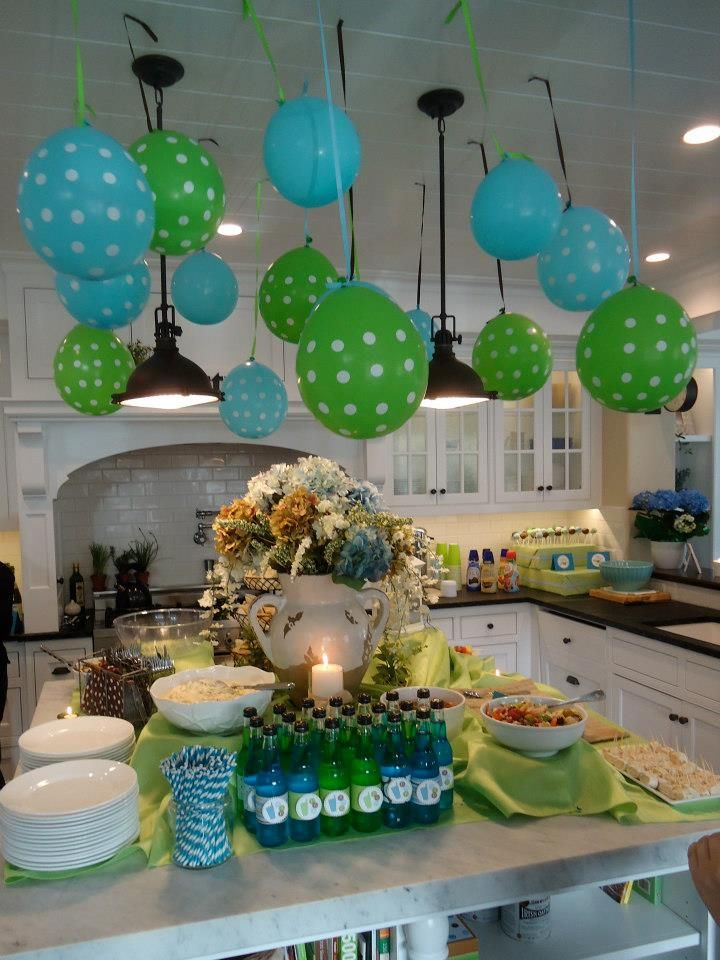 """Kitchen area. Balloons hung from the ceiling at various lengths, blue/green Jones sodas with Soda """"Pop"""" labels. Food such as """"Pop something healthy"""", Fruit """"Pops"""", Popcorn Chicken, etc."""