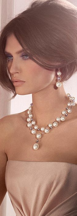 Large faux pearls alternating with round crystal or faceted glass beads. Lovely.