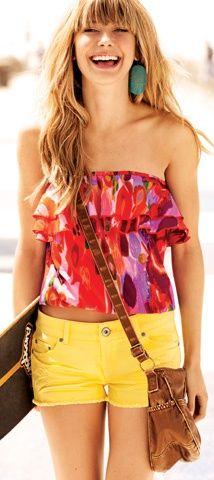 Summer outfit - colourful tube top, yellow shorts, braun leather handbag. Long blonde wavy hair.