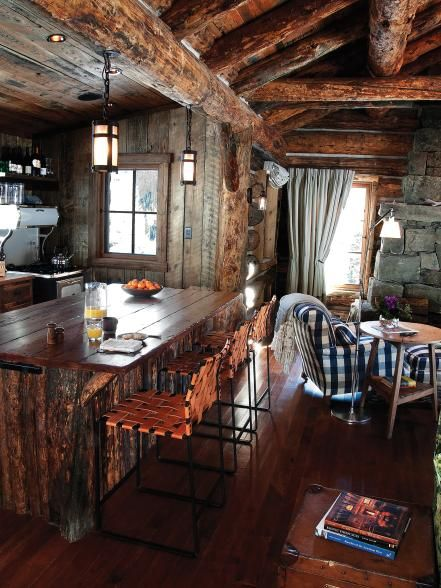 The kitchen island is made from recycled pine trees and rough cut pine boards. Iron bar stools with woven leather seats and backs provide seating for the island.