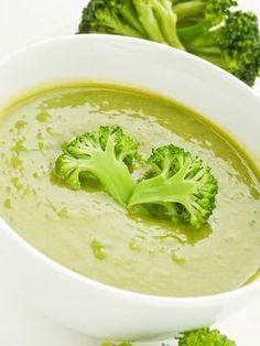 Een kom lekker verse broccolisoep volgens een recept van Jeroen Meus en Ons Kookboek met extra broccoliroosjes geserveerd