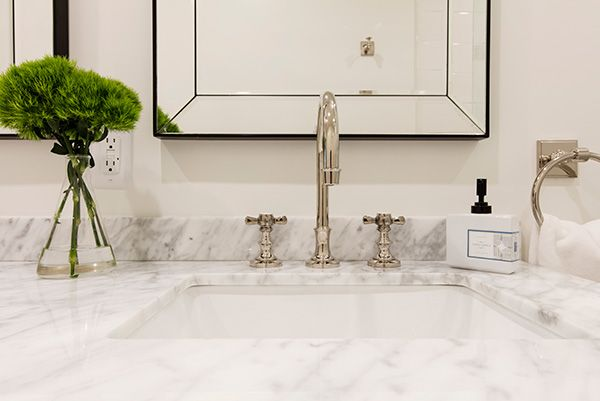 Luxurious bathroom renovation features a marble countertop sink and polished nickel fixtures.