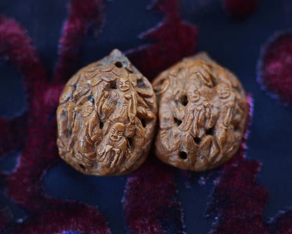 This is a vintage chinese carved netsuke style nut sculpture transformed into a stud earring pair. The two nuts are vintage, old chinese carvings. They are carved on both sides in GREAT detail. Really tiny monks are walking throo a forest and plants. Amazingly even their little faces and clothing are carved into this small piece. These rare sculptures are usually carved into fruit pits and nuts. These are I think a walnut taken apart into two halves. It is really a joy to look at all the…