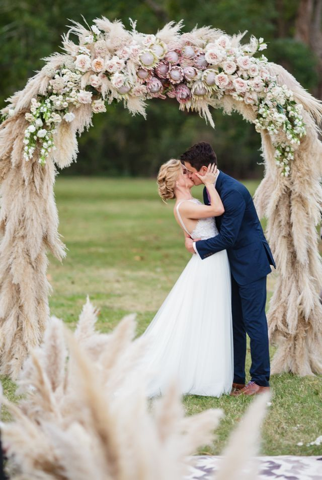 Most Dreamy Wedding Arch Ever | Muted Neutrals Wedding Ceremony Decor Ideas | Absolutely Stunning Wedding Ceremony Arch Decoration | Stunning Summer Wedding Inspiration for Outdoor Ceremonies | Gorgeous Outdoor Ceremony Backdrop for Weddings | Feathered Dry Grass Wedding Arch | Beautiful and Unique Wedding Ceremony Backdrop