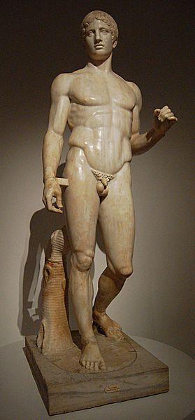 Policleto - Doriforo - ca 450 a.C. - copia romana in marmo da originale bronzeo - Napoli, Museo Archeologico Nazionale. L'atleta è colto durante il movimento: è gravitante sulla gamba destra, mentre quella a sinistra è in riposo; il bacino si solleva dalla parte della gamba portante e si abbassa dall'altra, le spalle invece hanno un moto inverso.