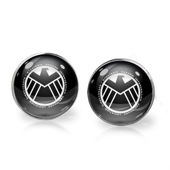 This listing is for ONE pair of SHIELD stud earrings inspired by Marvels Agents of SHIELD. A perfect gift for the fangirl in your life!   These earrings measure 14mm in diameter and utilise glass domes to magnify high quality images set beneath. They are made using high quality surgical steel ear posts for sensitive ears. This listing is part of our Buy THREE get ONE free promotion. Purchase any three pairs of earrings in the promotion and receive one pair of your choice free. Please DO NOT…