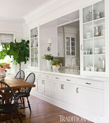 By expanding onto the old porch, the pre-renovation exterior window became a pass-through from the kitchen to the new breakfast room; it's flanked by built-ins that keep everyday dishes and linens at hand. What a great use of an old porch turned fabulous storage and breakfast room!