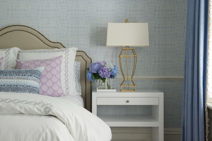 Gorgeous bedroom boasts walls clad in blue textured wallpaper accented with chair rail framing an arched linen headboard with brass nailhead trim on queen bed dressed in white and gray chain link bedding, lavender pillows and blue and gray lumbar pillow flanked by white lacquered nightstands topped with gold table lamps alongside a cream linen tufted bench placed at the foot of the bed
