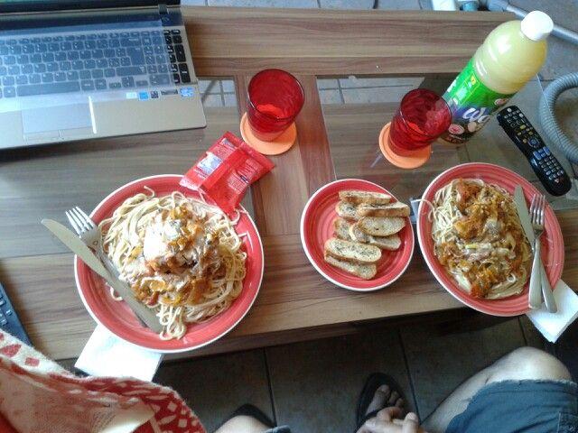 Tallarines con pollo a la crema y tomate con pan de orégano.