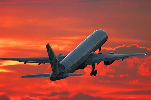 Commercial airplane climbing after take off in the sunset, via Flickr.