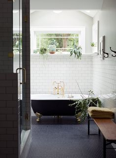 Open bathroom with white and black tile, gold finish freestanding bath tub, and plants.