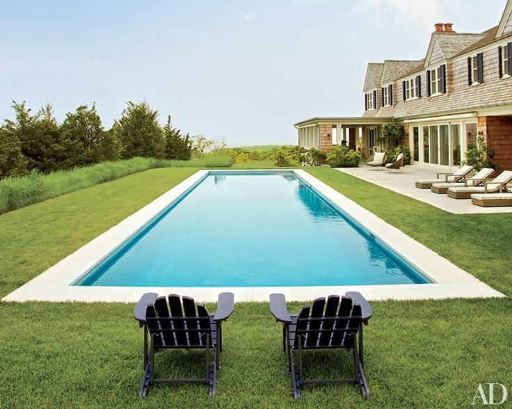 A minimalist swimming pool surrounded by twin Adirondack chairs and chaise lounges | archdigest.com