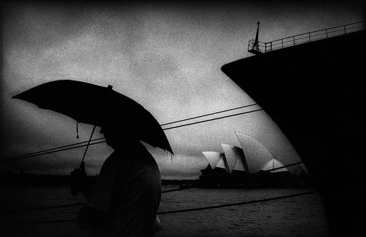 Trent Parke. AUSTRALIA. Sydney. A man stands in the rain at the overseas passenger terminal on Sydney harbour, which overlooks the Sydney Opera house. From Dream/Life series. 1999