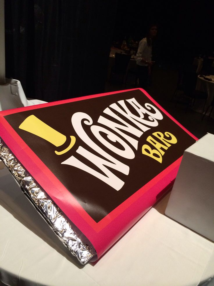 Make a giant wonka bar for the tv mike scene with foil, a poster size print out if the wrapper. Put it in large white round table with white linen.
