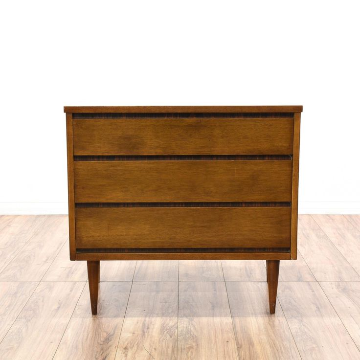 This short dresser is featured in a solid wood with a glossy walnut finish. This mid-century modern style chest of drawers has 3 spacious drawers with dovetailed joinery, sleek tapered legs, and simple straight sides. Perfect for storing clothing! #midcenturymodern #dressers #shortdresser #sandiegovintage #vintagefurniture