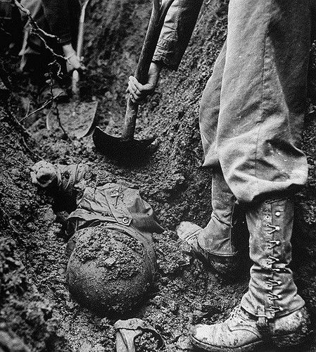 Retreating medical convoy team digging up body of American medic who was buried in landslide caused by German bomb during Battle of the Bulge fighting. 1945.