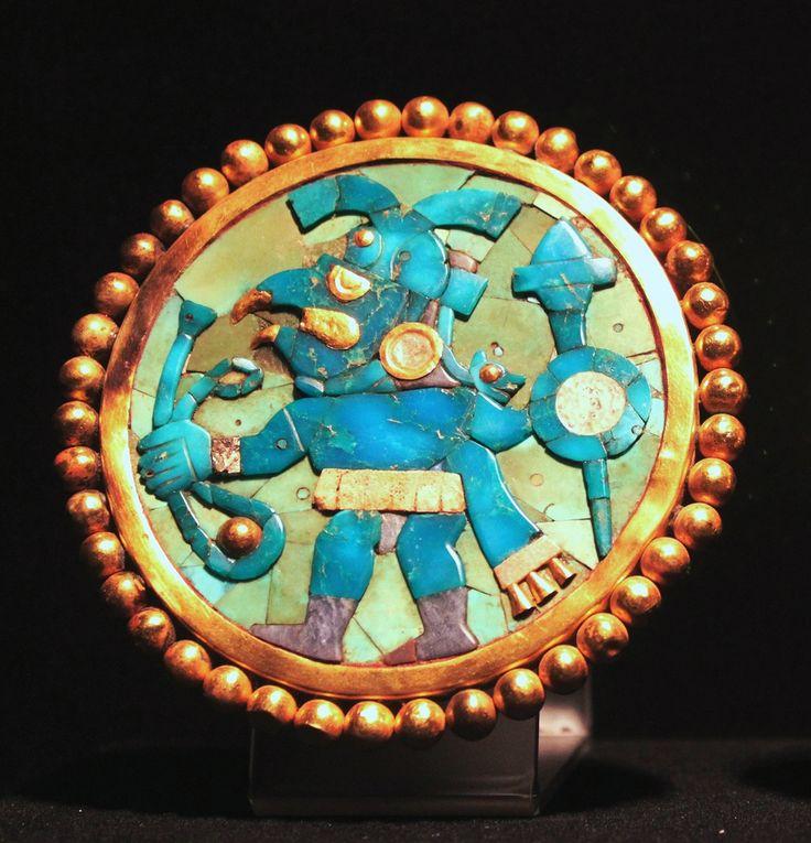 AncientMoche (Mochica) culture gold ear ornament,(Era Rise; 1 AD - 800 AD).  ornamento para las orejas que representa un guerrero con su tocado de plumas y cabeza felina. Perú.
