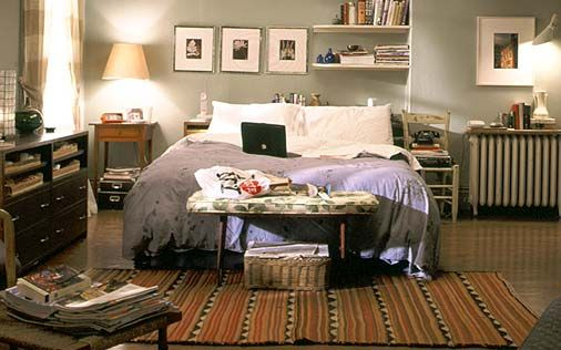 Carrie Bradshaw's bedroom. Showing that grey is just a wall colour, and it's what you do with it that matters! The picture frames and rug keep this homely.