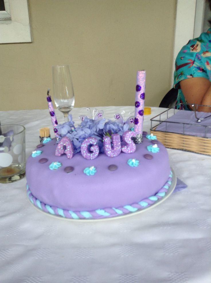 Torta de cumpleaños con flores. La torta tiene forma de rosquilla en el hueco hay un vaso plástico con agua donde se colocan las flores