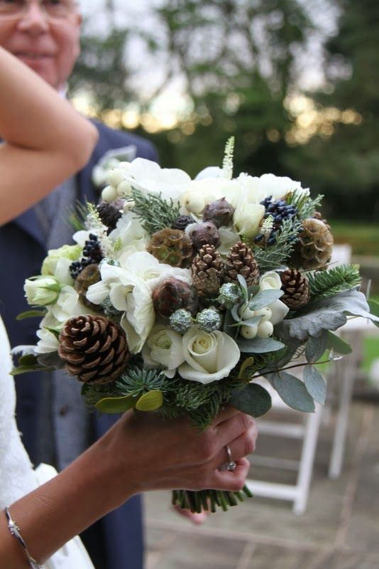 Wedding Bouquet of White Anemones, Ranunculas, Roses, Christmas Roses, Paper Whites, Snow Berry, Senecio, Kochia, Mistletoe, Eucalyptus Boules, Skimmia, Albiflora, Proteas,  Scabious Seed Heads, Viburnum Tinus, Fir Cones, Strobus and Blue Spruce
