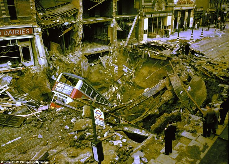 A double-decker bus is still visible amid the debris of a crater caused by a bomb which landed in Balham high street in October 1940.