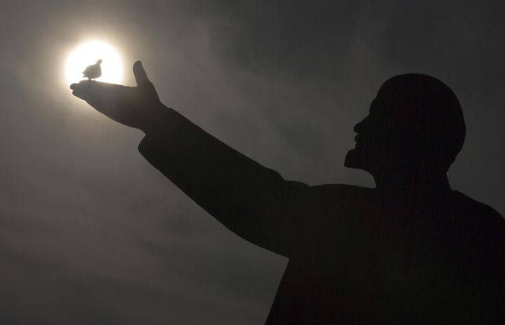 A bird silhouetted by the sun sits on the hand of a statue of Soviet Union founder Vladimir Lenin in the Baikonur Cosmodrome, Kazakhstan, on March 12, 2016.