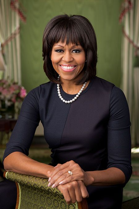 Obama facing forward, smiling, clad in black dress and single strand pearl necklace resting bare right forearm and both hands on a brocaded sofa armrest.