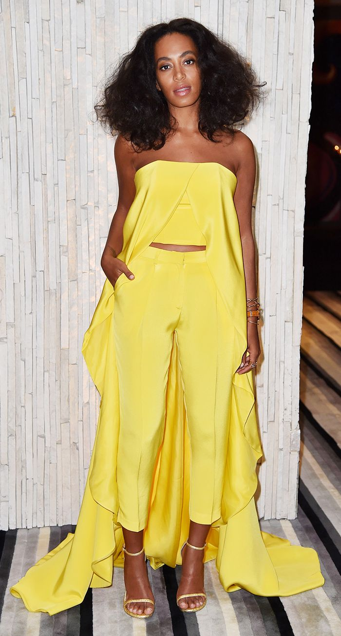 Solange Knowles pairs a bright yellow two piece suit with Stuart Weitzman heels