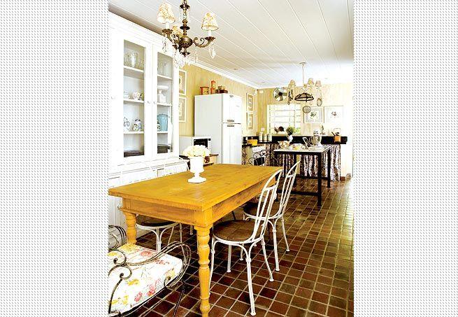A cozinha da foto anterior em outro ângulo: nas refeições em companhia de amigos, o morador usa todo o ambiente, dispondo o que vai servir sobre a mesa de ferro com tampo de mármore branco e os convidados sentam-se à mesa de madeira com cadeiras antigas
