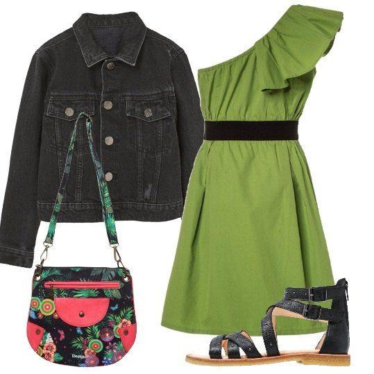 Outfit composto da vestito monospalla con volant e cinta, giubbotto di jeans nero, sandali bassi con cinturini alla caviglia e borsa multicolore Desigual.