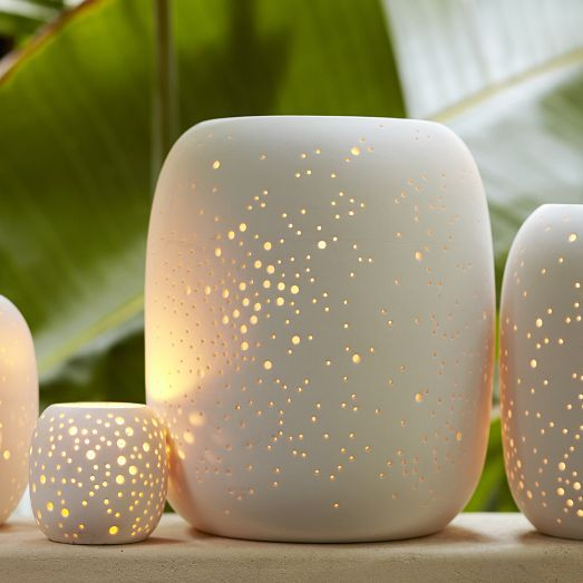 Cast a dappled glow. Crafted of porcelain, these picturesque Pierced Porcelain Lanterns are perforated with a delicate design inspired by the night sky that filters light in the loveliest way. 4 sizes + 2 colors!