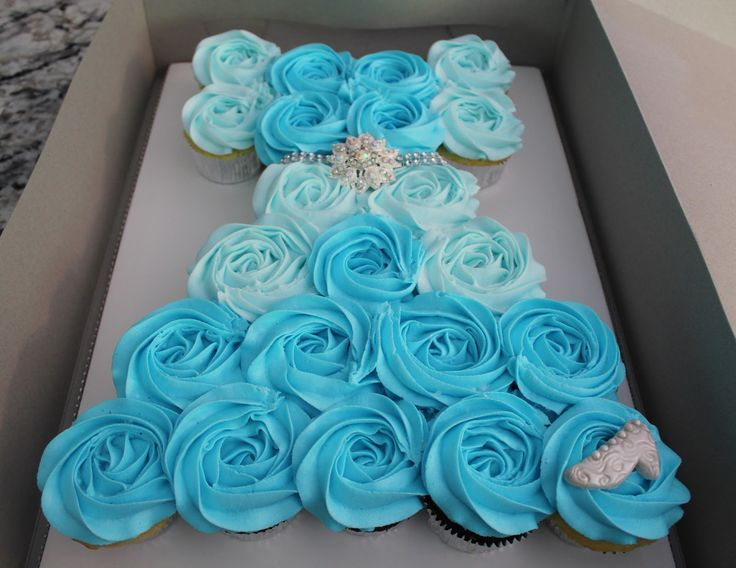 Cupcakes arranged as dress, blue icing foe Elsa's dress. Tiara and edible pearls, wand to decorate.