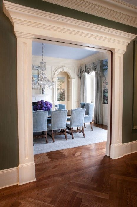 Stunning traditional dining room through a heavily framed double wide archway by Thomas Burak. Love how the green of the hall perfectly enhances the mural in the predominantly blue dining room. Don't forget about the lovely hydrangeas, velvet chairs, herringbone floors, and millwork either.