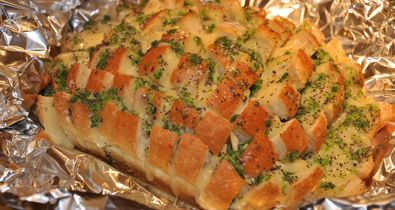 Gooey stuffed bread -1 unsliced loaf (round is preferable) sourdough bread - mine was square.  1 pound Monterey Jack cheese, thinly sliced  1/2 cup butter, melted  1/2 cup finely diced green onion, with tops  2-3 tsp poppy seeds