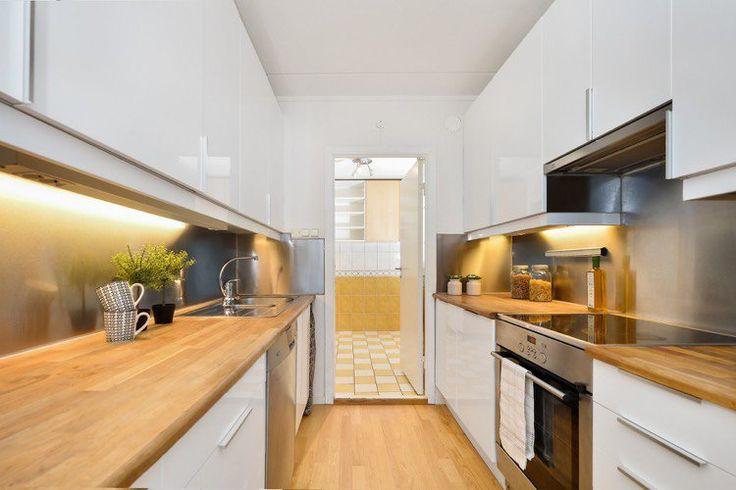 cuisine blanche en deux lignes équipée de crédences en inox, plans de travail en bois massif et parquet