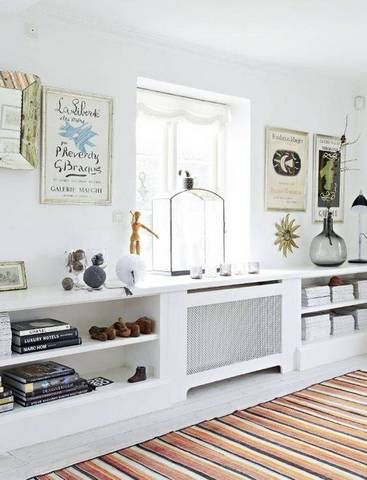 Stylish Radiator Cover Ideas For Summer | Domino -- This patterned cover blends in with the wall-to-wall shelving while lending a chic decorative element to the room.