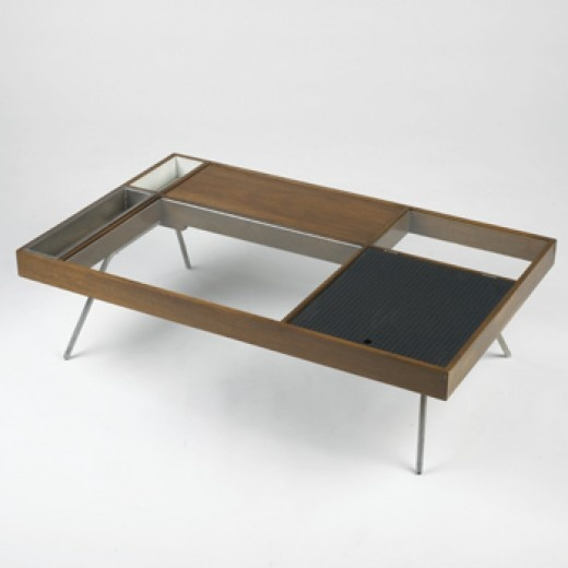 MILO BAUGHMAN    coffee table    Glenn of California  USA, c. 1955  walnut, glass, aluminum, nickel  48 w x 30 d x 12.5 h inches  The top of this table is a composition of varied material, colors and textures and is one of Baughman's best designs.