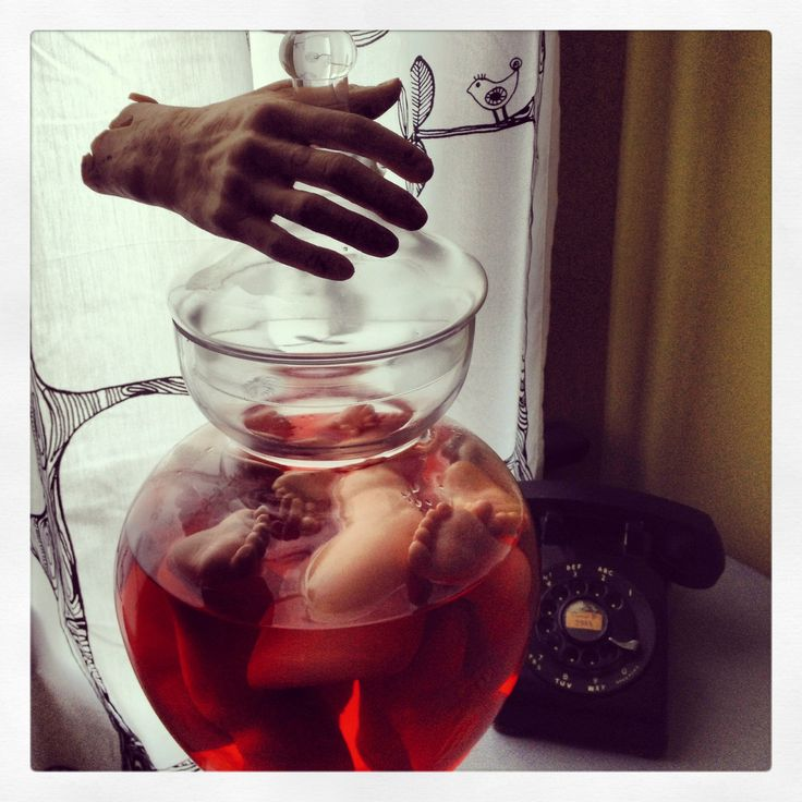 Glass jar with red food coloring water and babydoll parts. A severed rubber hand for added creepy effect - Halloween decoration display