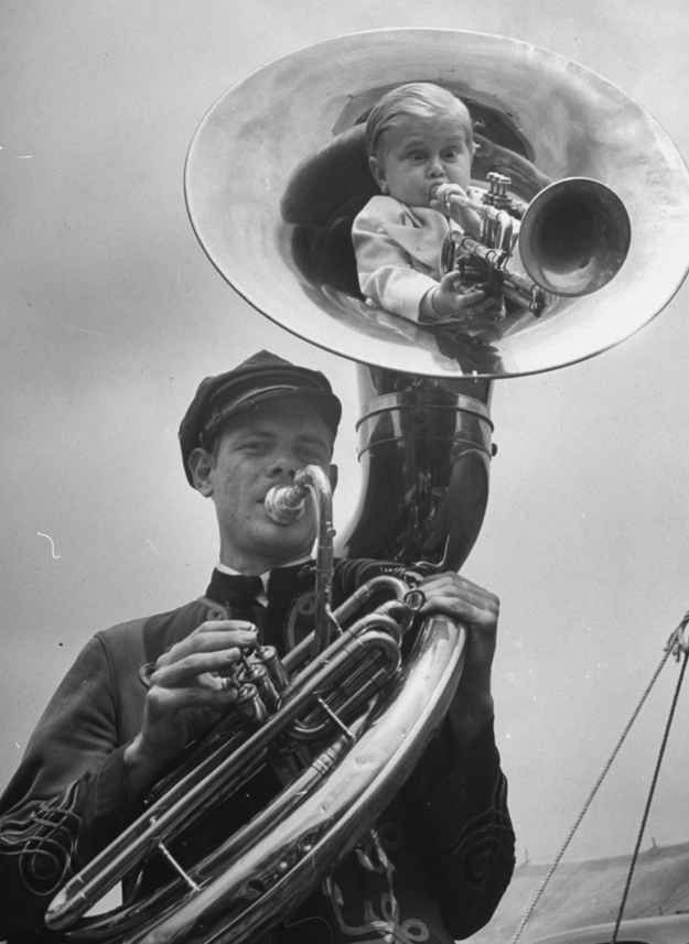 Czech showman Baron Richard Nowak, 19, stands 21 inches high & weighs 17 lbs., blowing on a trumpet as he nestles inside tuba player of the Hamid-Morton Circus. (1940)