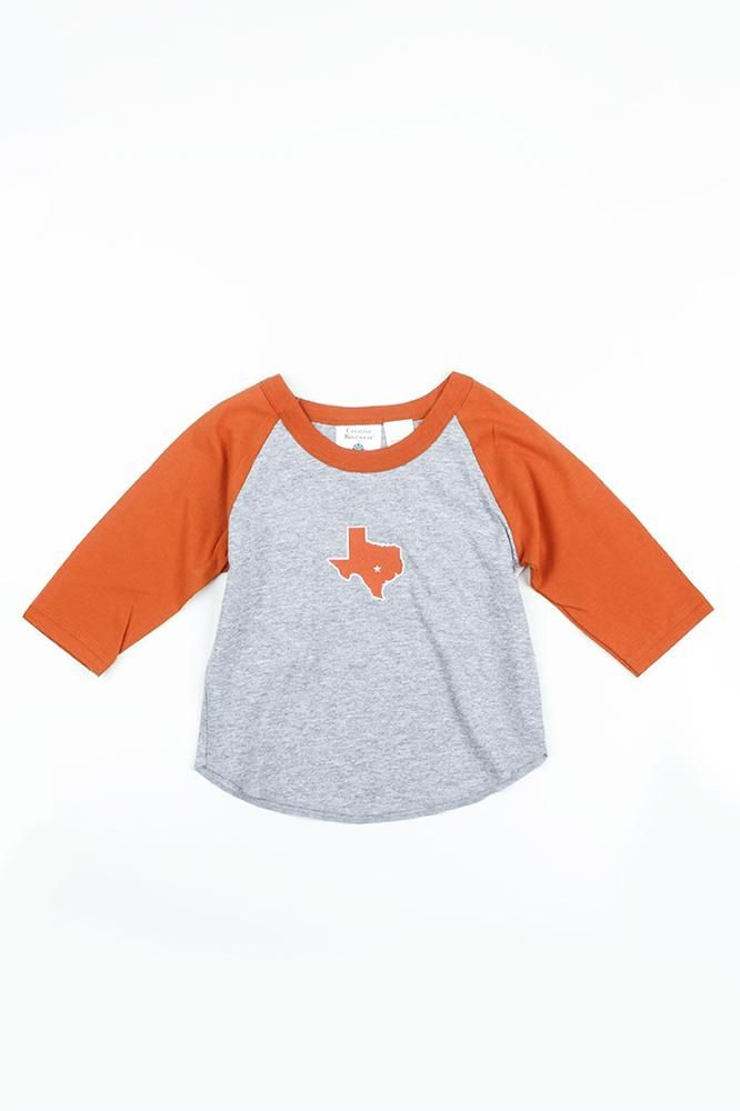 Give your little Texan a head start on their game day gear with this Toddler Texas Baseball Tee! This long-sleeve raglan t-shirt features Burnt Orange sleeves, a heather gray body, and a Burnt Orange patch on the chest in the shape of Texas with a star in the location of Austin.  90% Cotton / 10% Polyester
