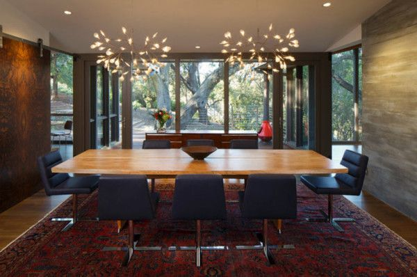 Architect David Henig remodeled this mid-century home in San Francisco with a dining room that looks out to a lot full of trees. Mimicking nature, two tree-like Heracleum II lights by Bertjan Pot for Moooi were installed above the wooden table.