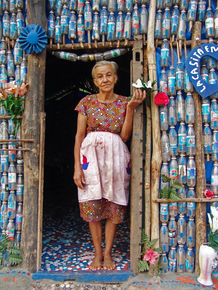 a home made of blue plastic recycled bottle cans and rough-hewn wood branches. La casita encantada, construida por Maria Ponce, San Miguel, El Salvador