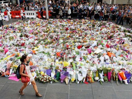 Sydney siege: Thousands pay tribute to victims killed in Martin Place Lindt cafe shootout Photo: Woman walks past flowers at Martin Place (Getty Images: Daniel Munoz)