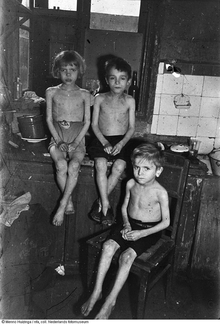 Drie uitgemergelde kinderen poseren tijdens de hongerwinter in een verwaarloosd interieur, Den Haag (1944-1945) Menno Huizinga