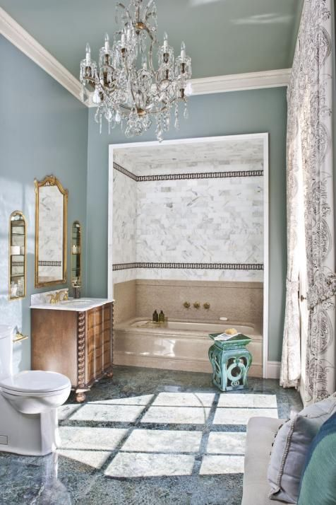 Varied marble finishes on the floor, tub and bath enclosure add richness and texture to this traditional master bathroom, part of a California showhouse. A pale, dusty blue on the walls gives way to a blue-gray ceiling, making the high-ceilinged space feel more intimate. Gold fixtures, dressy draperies and a crystal chandelier are lavish finishing touches.