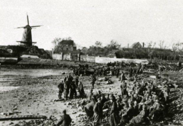Duitse krijgsgevangenen, bijeengebracht door geallieerde commando's in de Dokhaven, met op de achtergrond een molen. Vlissingen, nov. 1944